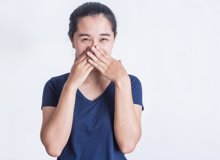 Asian woman covering mouth for bad breath on white background.