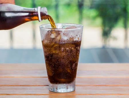 Cola drink is poured into a glass with ice. Banco de Imagens