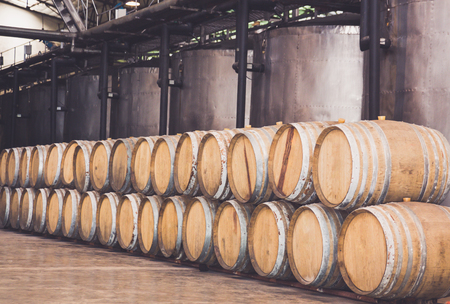 Wine barrels stacked in the wine cellar and large steel tank vessels on a factory,Thailand.