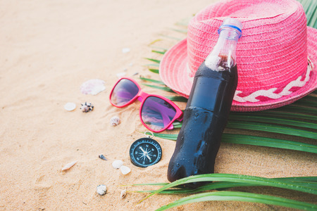 Carbonated soda bottle on sand at the beach,summer concept.