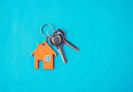 Casa e chiave su sfondo blu. Stile creativo minimale. Archivio Fotografico