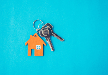 House and key on blue background. Minimal creative style.