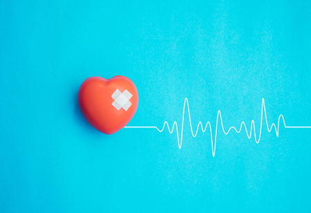 Red heart with bandage on blue background,Healthcare concept.