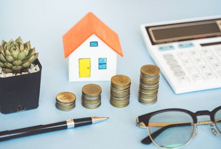 House model,coin and calculator on blue background for finance banking concept.