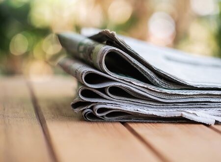 Pile of Daily newspaper on the wooden table with nature abstract background.