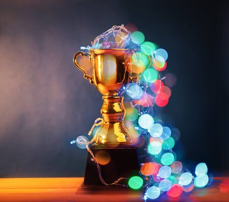 Win concept, gold trophy cup is winner in a competition with abstract bokeh background.