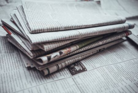 Pile of Daily newspaper on table,blur abstract background.
