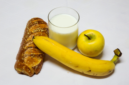 Pastry, Banana, Aplle and Glass of Milk Isolated on White Background. Healty breakfast, roll with sesamo and glass of fresh milk. Backery, bread, breakfast.