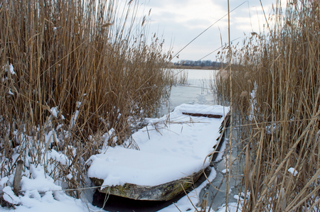A boat full of snow stands between reed on a frozen lake in a cold winter day Stock Photo