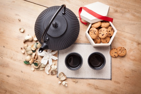 Chocolate biscuits with teapot and mugs, wooden background photo