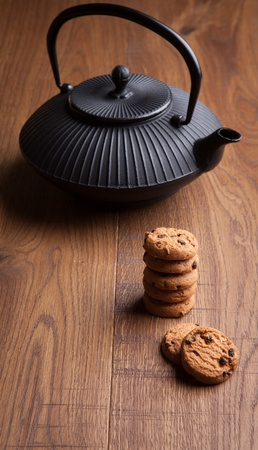 Japanese teapot with chocolate biscuits, wooden background photo