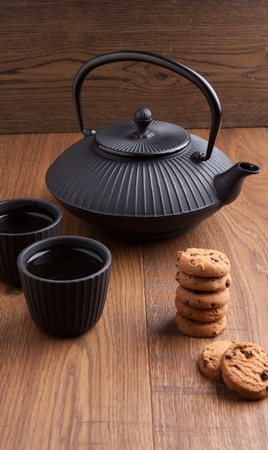 Japanese teapot with chocolate biscuits and cups, wooden background photo