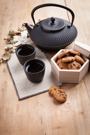 Japanese teapot with chocolate biscuits in a box and cups, wooden background photo
