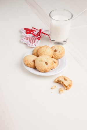 Biscuits on a plate with milk and hearts, breakfast on white background  photo