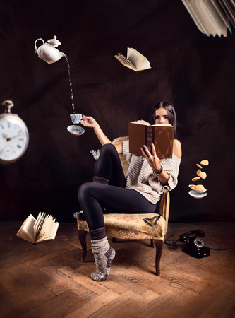 Young girl reading a book in a surreal situation with objects flying Stok Fotoğraf