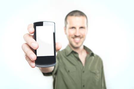 Youn man on white background showing a smart phone  Imagens