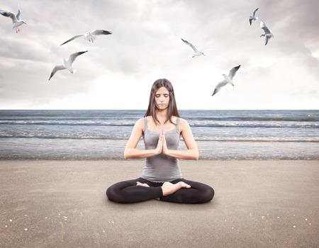Young girl doing yoga on the beach Stock Photo - 25720724