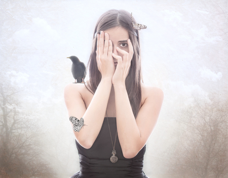 Young brunette hiding behind hands with butterflies and a bird on her