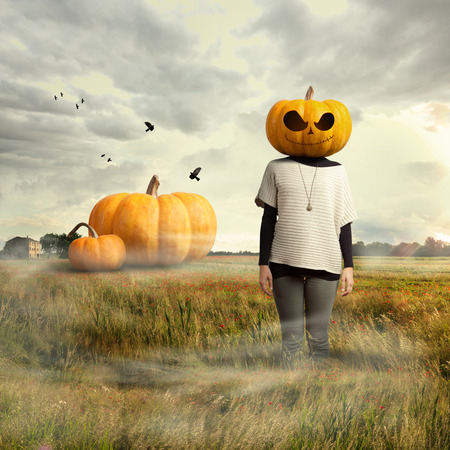 Young girl with pumpkin head, big pumpkins on the background, halloween time