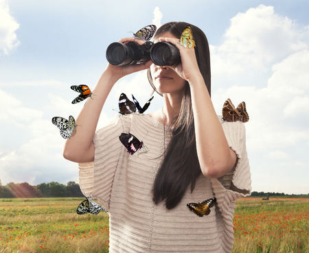 Young woman watching with binocular with butterflies Imagens