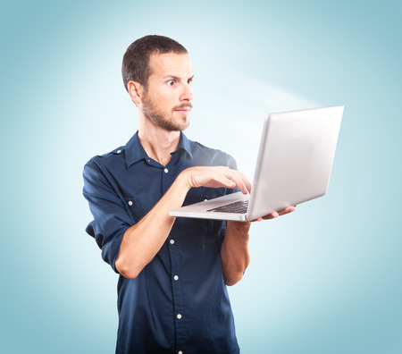Young man holding a laptop on blue background