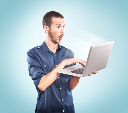 Young man surprised holding a laptop on blue background