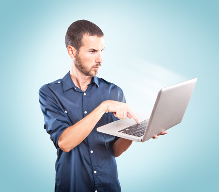 Young man focused holding a laptop on blue background