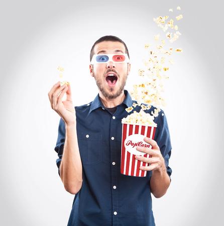 palomitas de maiz: Hombre joven que mira una pel�cula con gafas 3d y palomitas