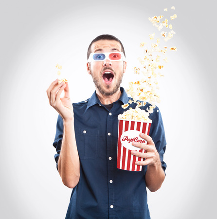 Young man watching a movie with 3d glasses and popcorn Stock Photo