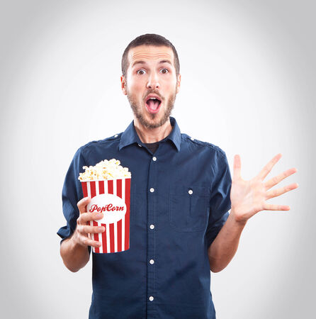 Young man watching a movie with popcorn