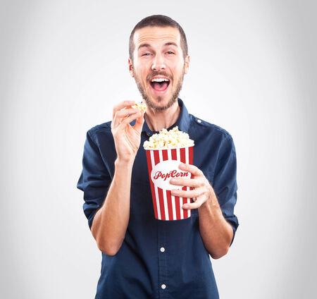 palomitas de maiz: Hombre feliz joven que mira la pel�cula y la celebraci�n de las palomitas de ma�z