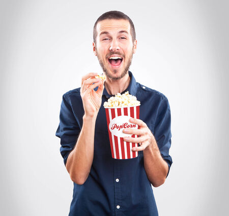Young happy man watching movie and holding popcorn