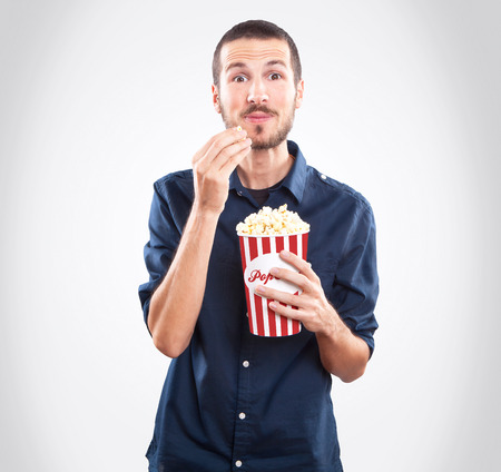 Young happy man watching a movie and eating popcorn