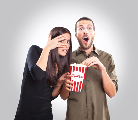 Young couple watching a movie and eating popcorn photo