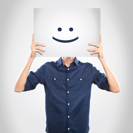 Young man holding a paper with a smile Imagens