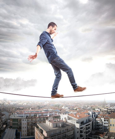 Young man walking on a rope in balance photo