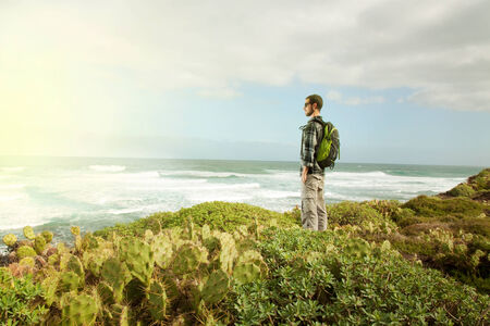 Young man standing in front of the sea Imagens