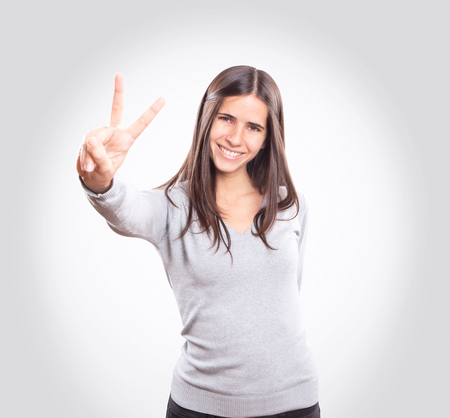 Young woman showing two fingers Imagens