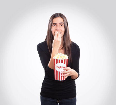 Brunette watching a movie and eating popcorn