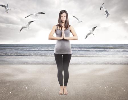 Young girl doing yoga on the beach Imagens