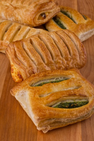Strudel with spinach and cottage cheese on wooden table