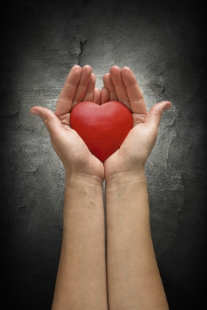 Woman hands holding heart over a dark concrete wall. Like a symbol of hope, love or peace.