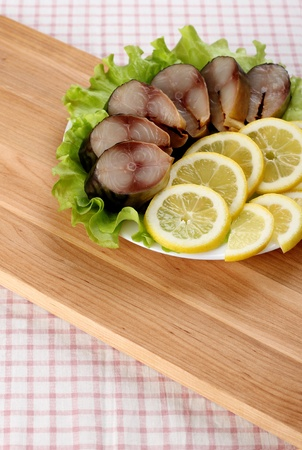 Composition with Smocked Mackerel Fish, Lemon and Salad Leaves on Wooden Table with Tablecloth.