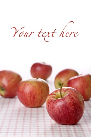 Red apples on tablecloth with white background for placing your text or design elements