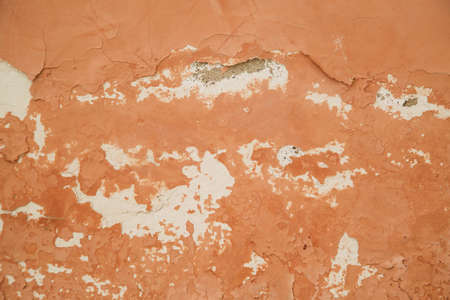 wall with peeling terracotta paint close-up, texture.