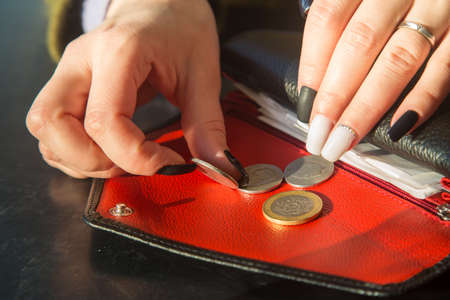 womens hands with a beautiful manicure take coins from a leather wallet.