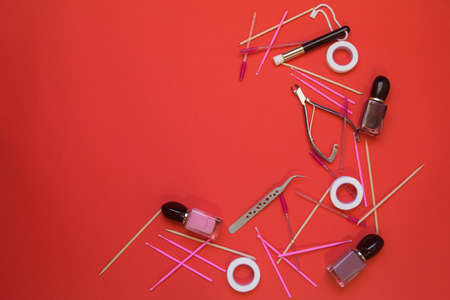 items for eyelash extensions and manicure on a red background