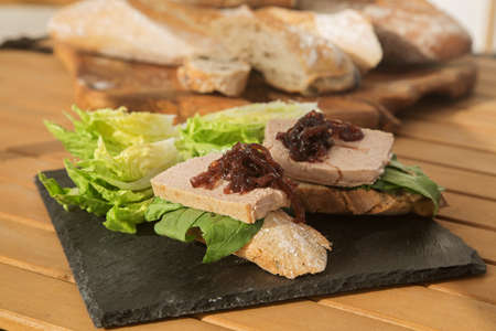 bruschetta with liver pate and onion jam on a black plate and wooden table