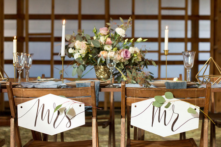 Wedding party. Laid Table by wedding banquet in a wooden barn. Candles and bouquet. Vintage Style. Фото со стока