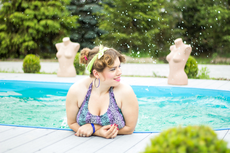 Young beautiful plus size model splashing in the pool, xxl woman portrait, professional makeup and hairstyle Stock Photo